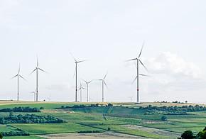 Windräder auf grünen Feldern.