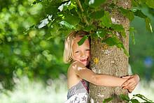 Maedchen umarmt Baum.