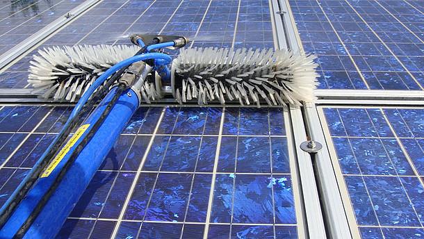 Solarmodule und Gerät zur Reinigung: Stiel mit Wasserschlauch und Stromkabel, vorne zwei Bürsten, mittig Spritzdüsen