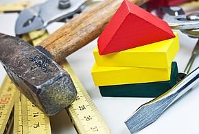 Symbolbild für KfW-Förderung: Hammer, Zollstock und andere Werkzeuge mit bunten Holz-Bausteinen