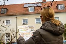 Frau schaut sich vor ihrem Haus einen Energieausweis an.