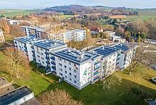 Mehrfamilienhäuser mit Solaranlagen auf den Dächern aus der Vogelperspektive.