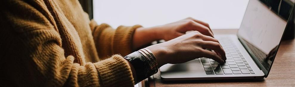 Frau sitzt am Laptop