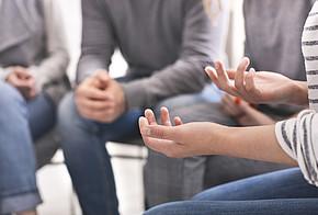 Menschen sitzen im Kreis und beraten sich