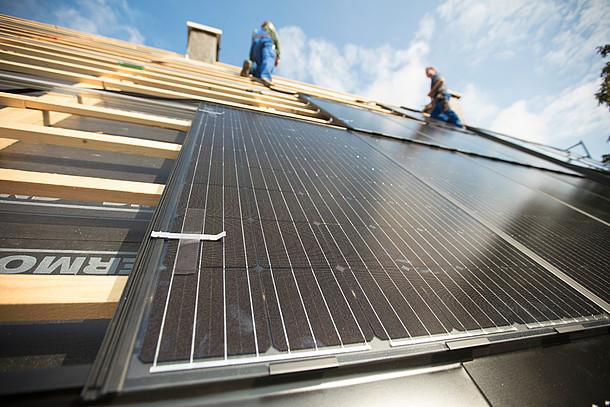 Installation von Photovoltaik auf einem Dach: Module auf Dachlatten von unten fotografiert, oben Schornstein und zwei Handwerker